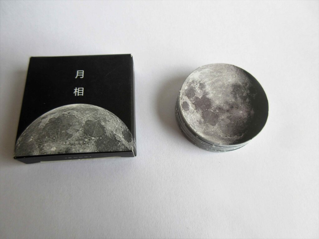 Moon stickers stacked over one another, along with a box containing a moon design