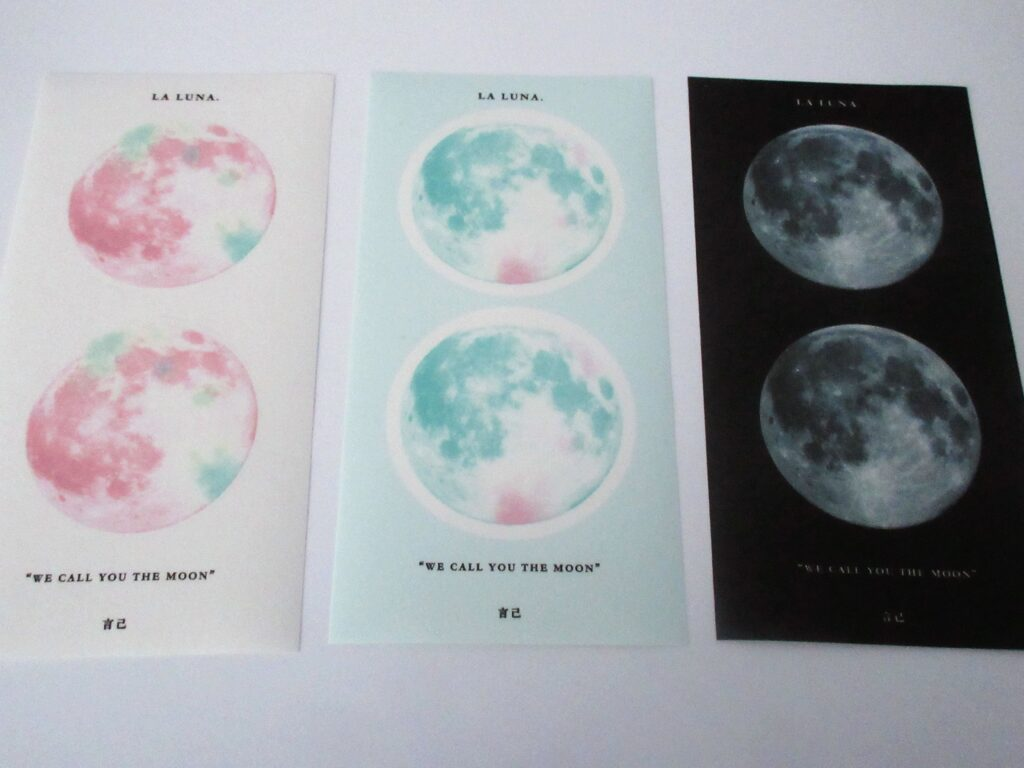 Three sticker sheets, each with two moons. The first shows pink pastel moons, the second has light blue moons on a light blue background, and the third has moons on a black background