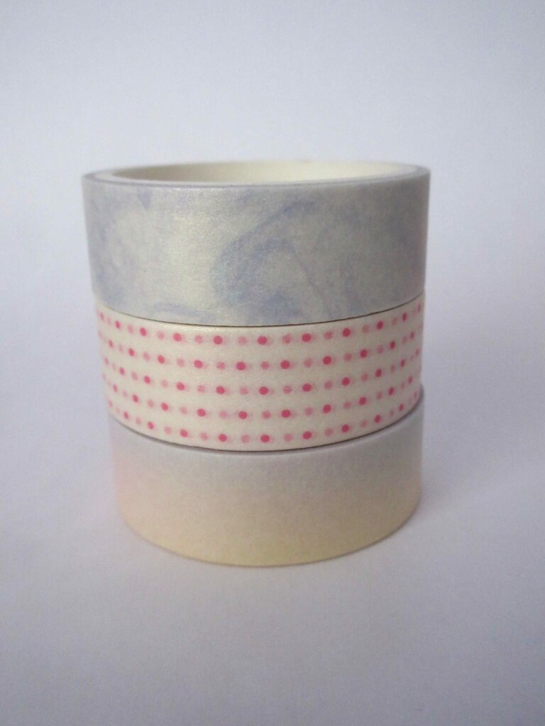 Three pastel tapes, one tape with a gradient, the second with pink polka dots, and the third with a blue swirl effect