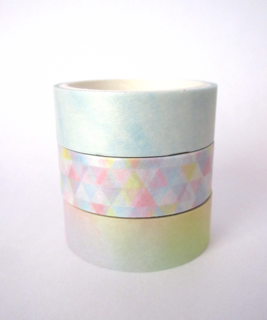 Three pastel washi tapes, the first is a pale blue washi tape, the next features triangles in pastel colors and the third features a rainbow gradient